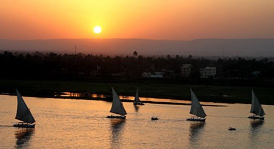 Feluccas Ending Another Day: Sunset on the Nile in Luxor, Egypt